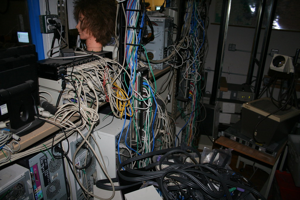 A cluttered room filled with a large number of computers, cables, and various media equipment